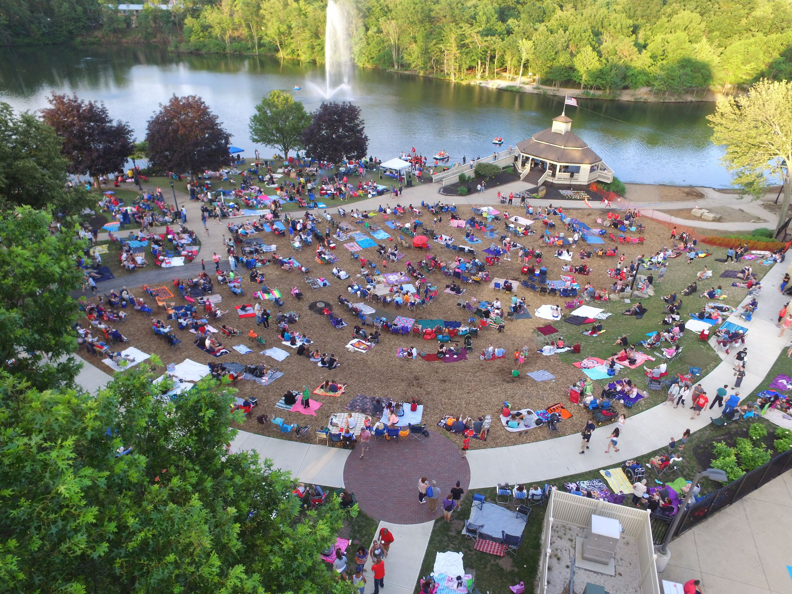 People sitting on the lawn of Coe Lake Park at the Grindstone Festival